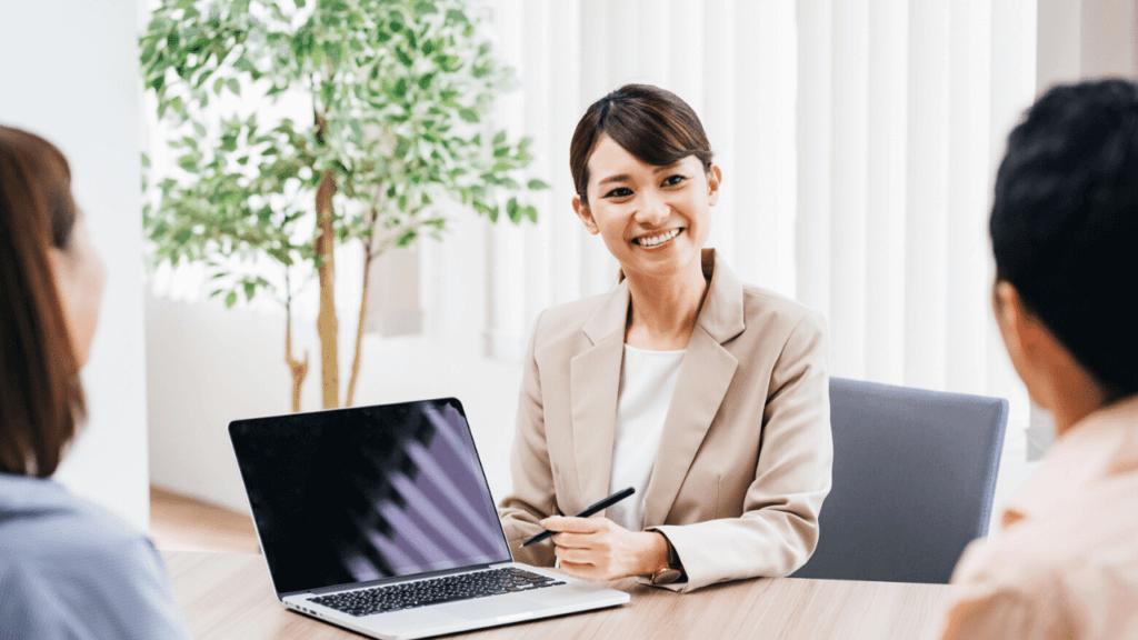 パソコンを使って団信保険について説明する女性