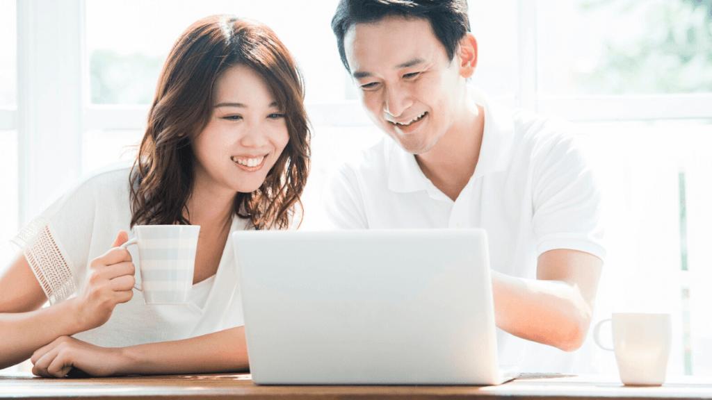 満足そうにパソコンで物件情報を見ている夫婦
