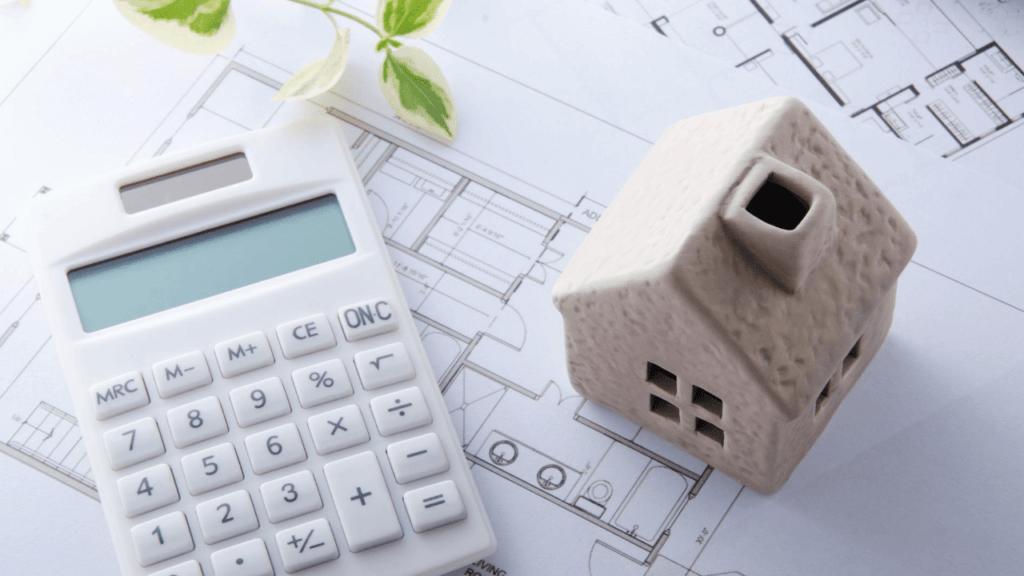家の模型と電卓と間取り図