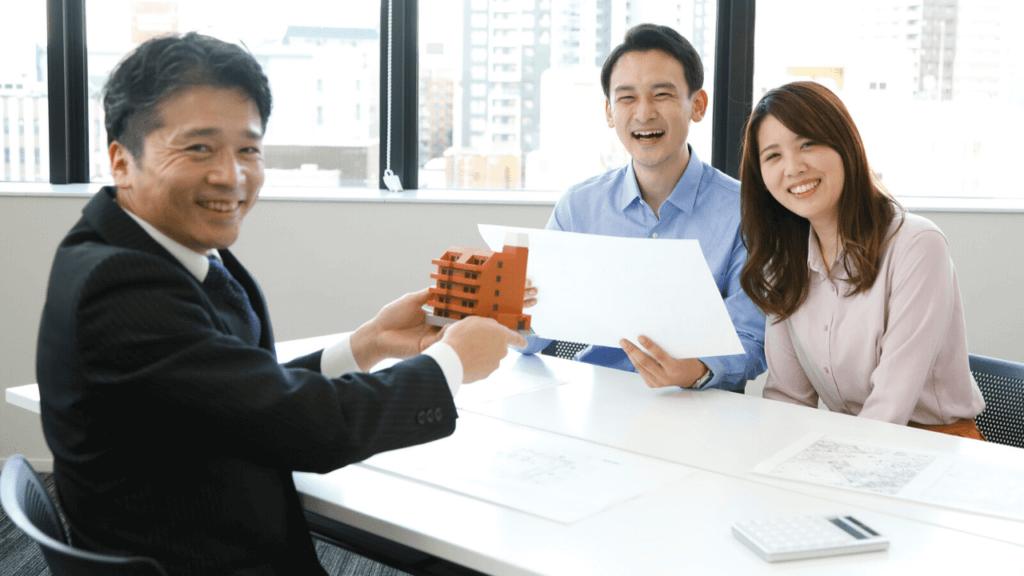 不動産投資アドバイザーと満足そうなお客の夫婦