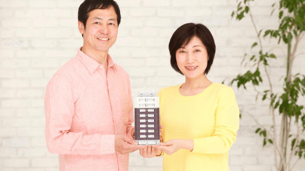 マンションの模型を持つ笑顔の夫婦