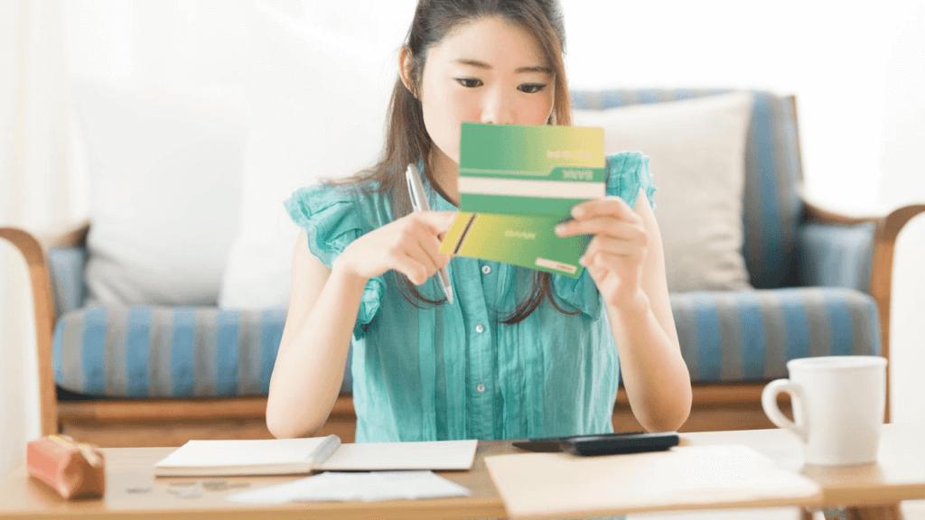 通帳を確認する若い女性